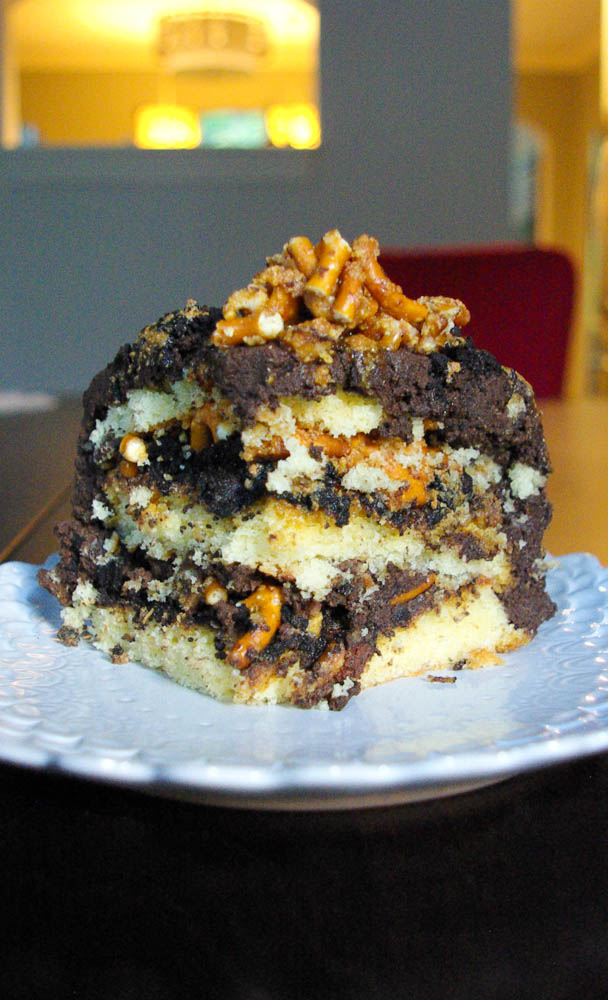 Salted Caramel Pretzel Chocolate Cake | Vanilla Chocoalte Chip Cake with Pretzel Crunch, Chocolate Crumb, and Caramel Sauce between the layers, with Chocolate Fudge Frosting on top. Truly a decadent masterpiece of a cake.