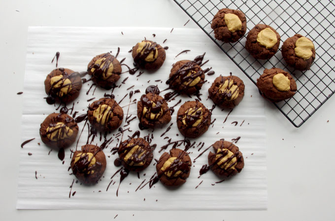 Buckeye Thumbprint Cookies - dense chocolate cookie base topped with a sweet peanut peanut butter ball and drizzled with bittersweet chocolate | www.thebatterthickens.com